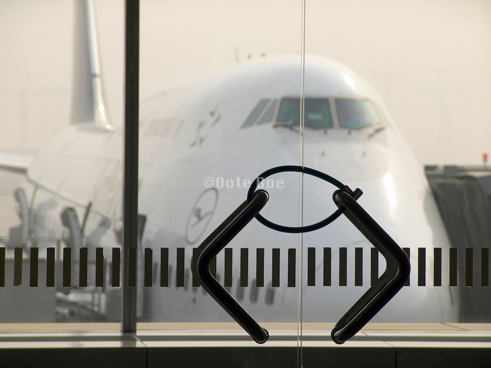 a big airplane seen through a glass door locked with a small chain lock