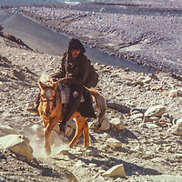 A horseman rides up a trail in the Kali Gandaki Valley, Nepal.