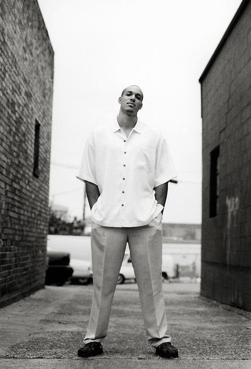 Portrait of a man posing in an alley.