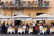 Diners eating outide under large shade umbrellas at the Tre Scalini Restaurant in Piazza Navonna, Rome, Italy.