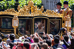 The Queen looks out at the crowd as she leaves Parliament in her carriage.