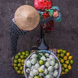 Street vendors from above, Hanoi - Vietnam Streetsellers, Hanoi (from above). <br /> <br /> Like most of her colleagues, this lady is an early riser and cycles from the outskirt into Downtown Hanoi to sell her fruits.I spent hours and hours on bridges, it took me some days to find the right spot. Depending on the colorful arrangement some streetseller are more promising than others. Some are brining in their mobile kitchen to prepare food on the spot. Others offer loads of clothing or even haircuts. There is the coffee guy, flower an veggie ladies, the shoe-shine boy, a karaoke singer duo. One morning I witnessed an old lady pulling a huge mobile scale for instant weighing.