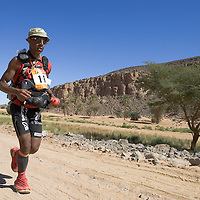 27 March 2007: #13 Karim Mosta of France runs across the gorge of El Maharch during third stage of the 22nd Marathon des Sables between jebel El Oftal and jebel Zireg (20.07 miles). The Marathon des Sables is a 6 days and 151 miles endurance race with food self sufficiency across the Sahara Desert in Morocco. Each participant must carry his, or her, own backpack containing food, sleeping gear and other material.