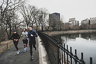 New York City, USA - March 19, 2020: Three joggers are out for a run at the Central Park reservoir in New York City.