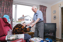 Elderly carer helping his wife with Alzheimer's disease out of the chair,