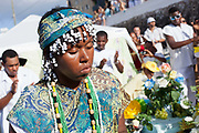 Young female member of a Candomble group in traditional green dress, being initiated in a public ceremony on the beach. February 2nd is the feast of Yemanja, a Candomble Umbanda religious celebration, where thousands of adherants visit the Rio Vermehlo Red River to make offerings of flowers and prayers, paying their respects to Yemanja, the Orixa goddess of the Sea and water.
