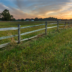 A wooden fence marks the edge of a field in Ipswich, Massachusetts.