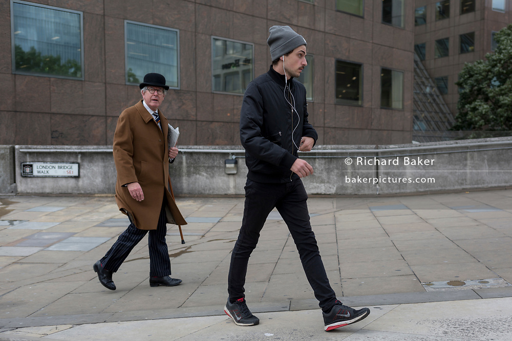 A city gent wearing a traditional but now a very rarely-seen bowler hat walks towards London Bridge rail station with a youth wearing a woolen hat and earphones, on 6th June 2017, on London Bridge, in the south London borough of Southwark, England. The griffin behind him is on the southern end of the Thames crossing but marks the southern boundary of the City of London, the capital's financial district.