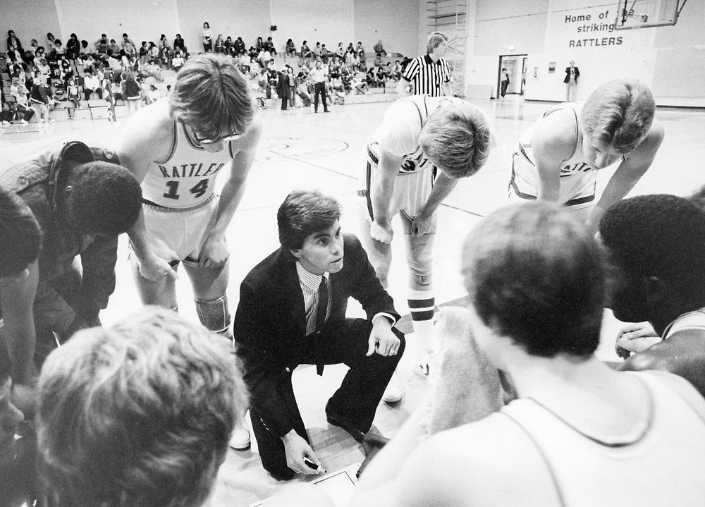 ©1985  Texas high school basketball coach talks to his team during a timeout, San Marcos, Texas