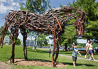 """Keegan Rodday of Hanover, MA reaches up to pet """"Horse"""" made by Rita Dee of Bennington, VT as part of Meredith's Sculpture Walk.  (Karen Bobotas/for the Laconia Daily Sun)"""