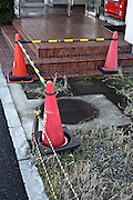red cones with bar blocking a grassy sidewalk leading to some steps