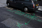 Sprayed parking notice on the ground in a City of London side street. As a polite message asking taxi drivers not to park on this spot, the unknown person wants this location kept clear between certain hours - something one driver has chosen to ignore because it is a place for cabs to pick up fares beneath the newest of London's skyscrapers, known as the Walkie Talkie in the heart of the capital's financial district aka The Square Mile. The green lines and lettering looks prominent but seems to be ineffective as a means of asking for clear space.
