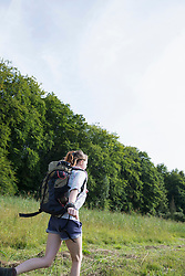 Young woman running with backpack in a forest, Bavaria, Germany