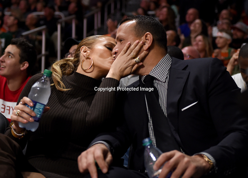 Jan 15, 2018; Coral Gables, FL, USA;  Recording artist Jennifer Lopez (left) and former New York Yankees baseball player Alex Rodriguez kiss during an NCAA basketball game between the Miami Hurricanes and the Duke Blue Devils at Watsco Center. Mandatory Credit: Steve Mitchell