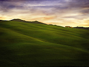 A farmhouse atop the rolling grassy green hills of Tuscany Italy.