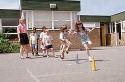 Junior school children playing games in playground,