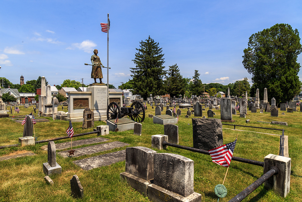 """Carlisle, PA – June 26, 2016: The Mary Ludwig Hays - better known as Molly Pitcher - gravesite, located in the Old Graveyard Cemetery, includes a statue of """"Molly"""" standing alongside a cannon."""