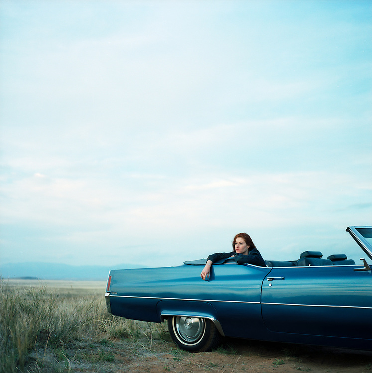 Young woman, 20 something, in back of vintage convertible, looking out at horizon.