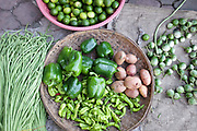Fresh fruit and vegetables: snake beans, limes, green peppers, green chillis, egg plant (aubergine) and potatoes for sale at Daeum Kor morning market in Phnom Penh, the capital city of Cambodia. A large variety of local products are available for sale in fresh markets all over Cambodia, all being sold on small individual stalls.