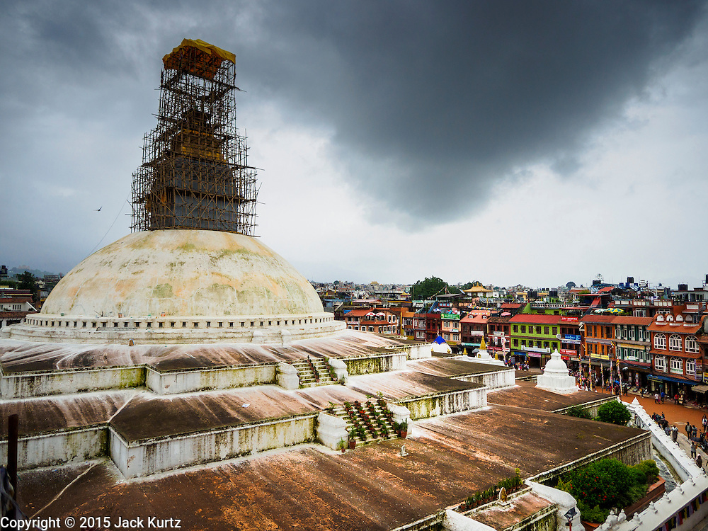 31 JULY 2015 - KATHMANDU, NEPAL:   Bodhnath Stupa in the Bouda section of Kathmandu is one of the most revered and oldest Buddhist stupas in Nepal. The area has emerged as the center of the Tibetan refugee community in Kathmandu. On full moon nights thousands of Nepali and Tibetan Buddhists come to the stupa and participate in processions around the stupa. The stupa was heavily damaged in the earthquake of 25 April 2015 and people are no longer allowed to climb on the stupa, now they walk around the base and pray with butter lamps. PHOTO BY JACK KURTZ