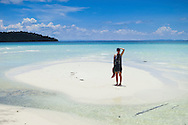 A woman stands on a idyllic deserted beach in Koh Rong Island, Cambodia, Southeast Asia