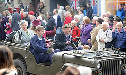 © Licensed to London News Pictures. 12/10/2014. Pickering, UK The annual wartime weekend in Pickering, North Yorkshire. People dress in 1940s period themed outfits and attend parades through the small Yorkshire town which has a traditional steam railway as would have been used in the 1940s. // Pictured:  The military vehicle parade through Pickering Market Place. Photo credit :  HARRY ATKINSON/LNP