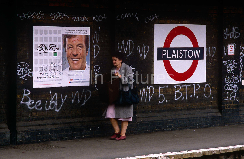 An elderly lady walks past the intimidating backdrop of tagged walls of Plaistow, an east London station after the crime of defacement and criminal damage to London Underground property has been committed by persons unknown - a persistent problem that costs the transport company network up to £3 million a year to remove. If caught, juvenile delinquents may escape with only a caution because of their age but older ones are prosecuted, though some times after leaving many thousands of tags across their neighbourhood.