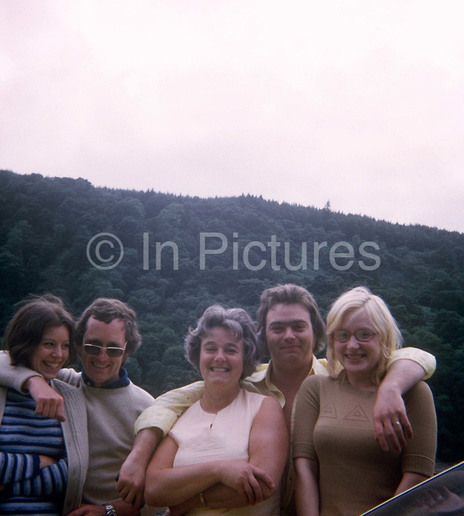Friends and family portrait with Welsh hills in the background in the 1970s. With an evergreen forest behind them, we see two couples accompanied by the mother of the man whose arms are draped over his wife's and his mother's shoulder. It was taken on a film camera by an amateur photographer in 1973. The picture shows us a memory of nostalgia in an era from the last century.