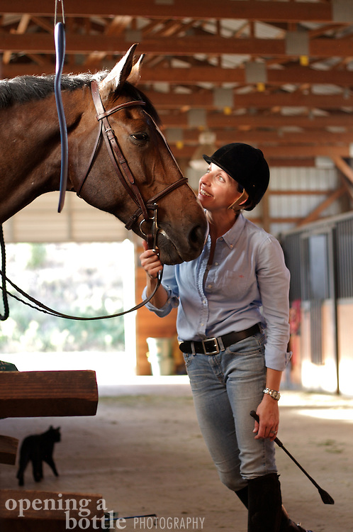 A female rider and her thoroughbred horse in the stable.