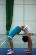A prisoner practices gymnastics at HMP Downview.