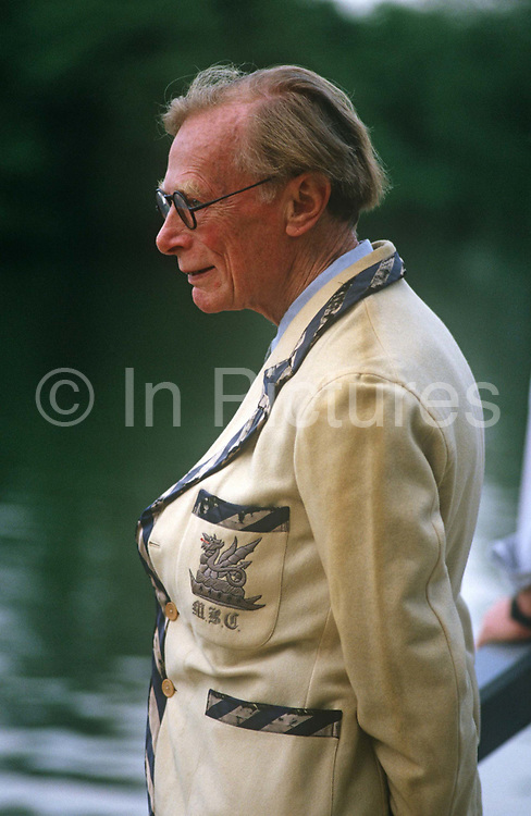 An elderly gentlemen member of an unknown rowing and sculling club looks at activity at the annual Henley-on-Thames boating festival. The elderly man stands slightly stooped wearing an exclusive blazer with his unknown club's badge on the breast pocket. He looks the quintessential Englishman, an aristocrat from a well-bred family whose heritage may well be from the highest of English society. This annual festival allows the high-society to watch serious rowing and general clowning around on the rural Thames. In 1829 a boat race challenge was held between teams representing the universities of Oxford and Cambridge. Now held July it is one of the main dates on the sporting calendar and social season for the hoi polloi.