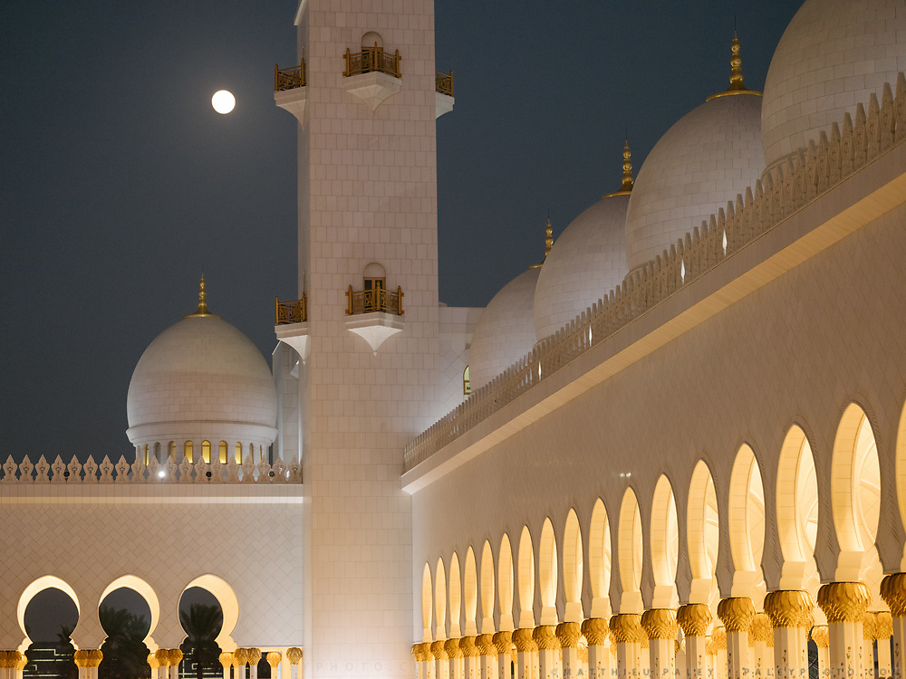 Full moon rising over the Sheikh Zayed Grand Mosque.