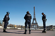 """March, 24th 2020 - Paris, Ile-de-France, France: French Police at Trocadero near Eiffel Tower controlling the movement of French citizens to prevent the spread of the Coronavirus, during the ninth day of near total lockdown imposed in France. A week after President of France, Emmanuel Macron, said the citizens must stay at home from midday on Tuesday for at least 15 days. He said """"We are at war, a public health war, certainly but we are at war, against an invisible and elusive enemy"""". All journeys outside the home unless justified for essential professional or health reasons are outlawed. Anyone flouting the new regulations is fined. Nigel Dickinson"""