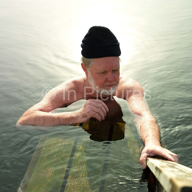 A man wearing a woollen hat relaxes in a hole in the ice after taking a sauna in the small lake Vuorilampi, Jyvaskyla, Central Finland.