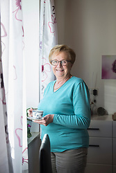 Smiling old woman at the window with a cup of coffee