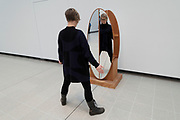 Visitors interacting with artworks at the Space Shifters exhibition at the Hayward Gallery on 16th December 2018 in London, United Kingdom. The exhibit was a major group show of sculptures and installations that explored perception and space, featuring 20 artists. Interactive Abstract Bodies Split Circle 2012 by Josiah McElheny.