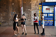 Stylish young women hanging out in Waterloo before a night out in London, United Kingdom. Dressed with each of their own individual style, they appear almost like a ready made girl band the ideal mix of styles and ethnicity.