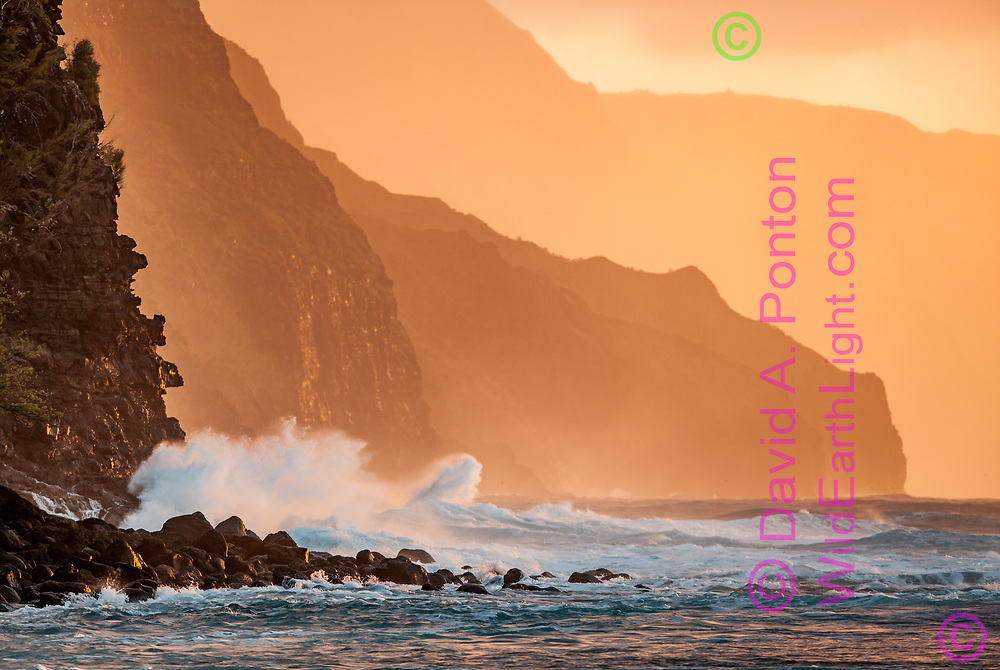 Ocean waves crash against cliffs on the rugged Na Pali Coast  in the light of the setting sun. Kauai, Hawaii, © David A. Ponton