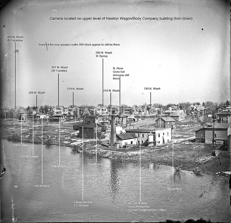 """Most buildings positively identified, a few might be wrongly identified.  View looking N.E. from the roof or upper floor of the Newton Wagon Company. Building with the tall chimney also appears in the 1869 """"bird's eye view"""" of map of Batavia.<br /> <br /> The dark building behind (east) of the building complex with the tall chimney still stands in the 100 block N. River directly accross the street from the bike path bridge. State Street would be on lot to the right (south) of that building."""