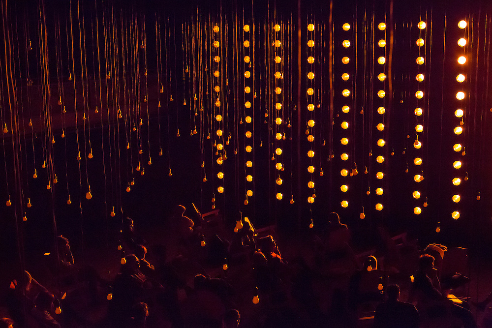 """A wall of orange lights, with pendant bulbs over the audience, in Samuel Beckett's """"All That Fall""""."""