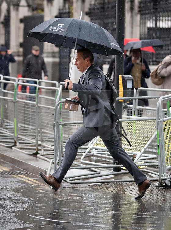 © Licensed to London News Pictures. 08/05/2019. London, UK. A man leaps over a puddle in Westminster in London as wet and windy weather hits the capital. Heavy rain is forecast for most of the UK this week. Photo credit: Ben Cawthra/LNP
