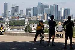 © Licensed to London News Pictures. 01406/2021. London, UK. Members of the public look out over the London Skyline during sunny weather in Greenwich Park . Temperatures are expected to rise with highs of 28 degrees forecasted for parts of London and South East England today . Photo credit: George Cracknell Wright/LNP