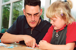 Father helping daughter with literacy skills