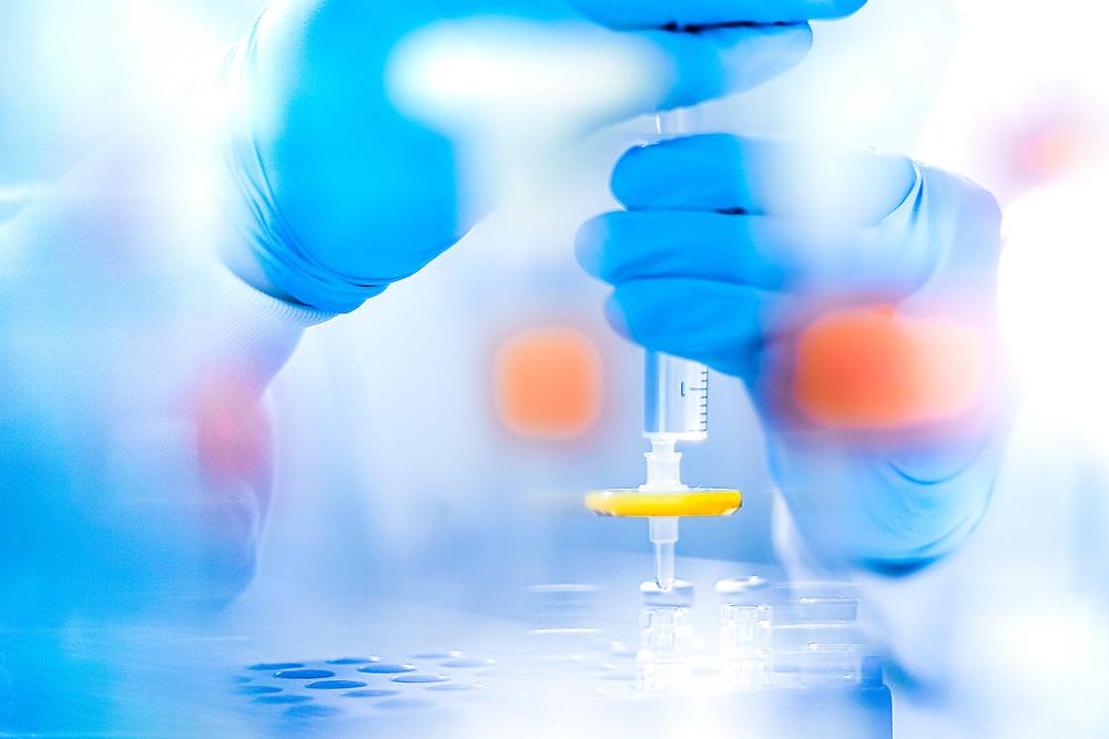 """Sanofi va aider Pfizer-BioNTech à conditionner son vaccin et promet """"plus de 100 millions de doses"""" d'ici la fin 2021.<br /> Une technicienne de laboratoire de l'usine de production de Sanofi analyse un processus de solution médicale.<br /> A lab technician at the Sanofi production plant analyzes a medical solution process."""