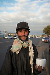 """Mark Schoeman, who lives on the streets, eats breakfast outside Thomas House of Hope, in Somerset West, Western Cape, on Tuesday morning, May 5, 2020. Thomas House normally provides programs through which people living on the streets can work in exchange for tokens that they can use for meals, ID books, clothing, toiletries and showers. But during lockdown, the centre has had to suspend its activities to simply serve meals to those who are hungry. """"Lockdown is hard because there is no work here,"""" he says. """"Normally, I get piece jobs. I do gardening, painting and tiling."""" PHOTO: EVA-LOTTA JANSSON"""