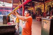 """12 APRIL 2012 - HO CHI MINH CITY, VIETNAM:  A Buddhist lights incense in Chùa Quan Âm (Avalokiteshvara Pagoda), a Chinese style Buddhist pagoda in Cho Lon. Founded in the 19th century, it is dedicated to the bodhisattva Quan Âm. The pagoda is very popular among both Vietnamese and Chinese Buddhists. Cholon is the Chinese-influenced section of Ho Chi Minh City (former Saigon). It is the largest """"Chinatown"""" in Vietnam. Cholon consists of the western half of District 5 as well as several adjoining neighborhoods in District 6. The Vietnamese name Cholon literally means """"big"""" (lon) """"market"""" (cho). Incorporated in 1879 as a city 11km from central Saigon. By the 1930s, it had expanded to the city limit of Saigon. On April 27, 1931, French colonial authorities merged the two cities to form Saigon-Cholon. In 1956, """"Cholon"""" was dropped from the name and the city became known as Saigon. During the Vietnam War (called the American War by the Vietnamese), soldiers and deserters from the United States Army maintained a thriving black market in Cholon, trading in various American and especially U.S Army-issue items.        PHOTO BY JACK KURTZ"""