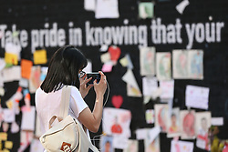 © Licensed to London News Pictures. 23/07/2021. Manchester, UK.  People take photographs of messages left on the mural of Marcus Rashford in Withington, Manchester. The messages are to be removed to Manchester Central Library for preservation. Photo credit: Adam Vaughan/LNP