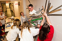 Jag students Jordin Poire, Jenna Dame, Mariah DeRoche and Lucy Tully duct tape Craig Kozens Athletic Director/Dean of Students to the wall to raise money for the Make-A-Wish foundation at Laconia High School Wednesday afternoon.  (Karen Bobotas/for the Laconia Daily Sun)