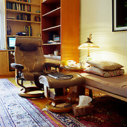 A large beige Stressless chair and footrest, the footrest holding a black notebook full of papers, in the middle of a room. There is a pinkish-beige couch and two square pillows to the right of the chair, a small circular table and an antique lamp with a shade producing a very beautiful diamond like pattern on the wall. Behind are bookcases and a computer screen is on, daylight streaming in from the left onto a large Oriental rug.