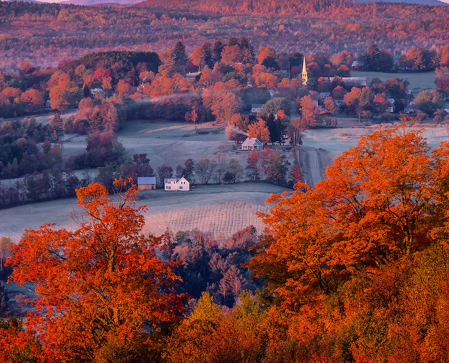 Fields and homes nestled around rural village with church steeple on hillside with fall foliage, Peacham, VT